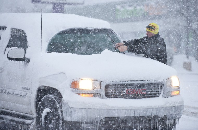 Image: A man cleans his windshield wipers off at a stop light in Bowling Green, Ky.