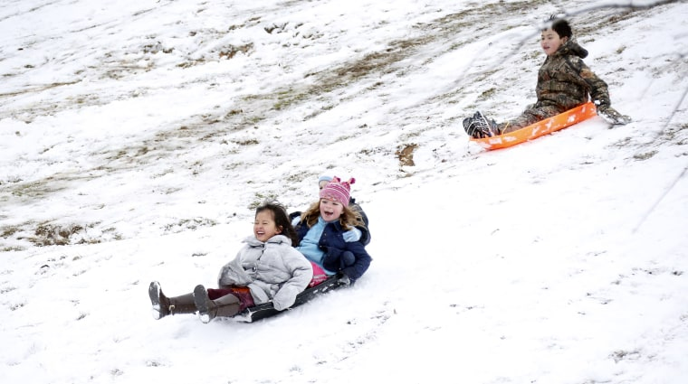 Image: Children sled down the hills in Avent Park