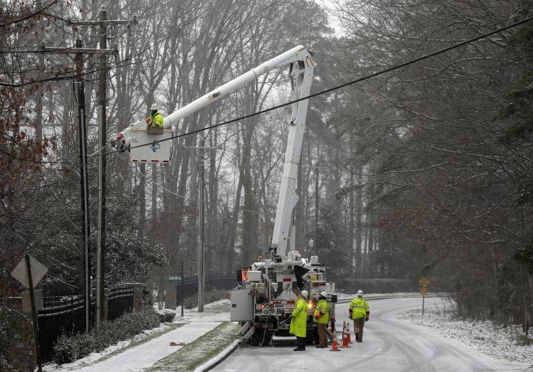 Image: Duke Energy employees work to restore power in a neighborhood in Matthews, N.C.