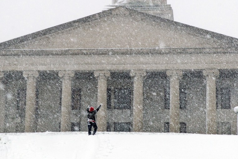 Image: A man celebrates making it up a steep, snow-covered hill in Nashville