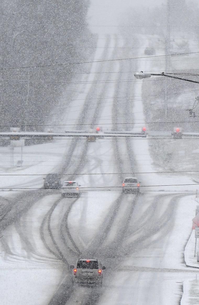 Image: Drivers make their way through falling snow in Franklin, Tenn.
