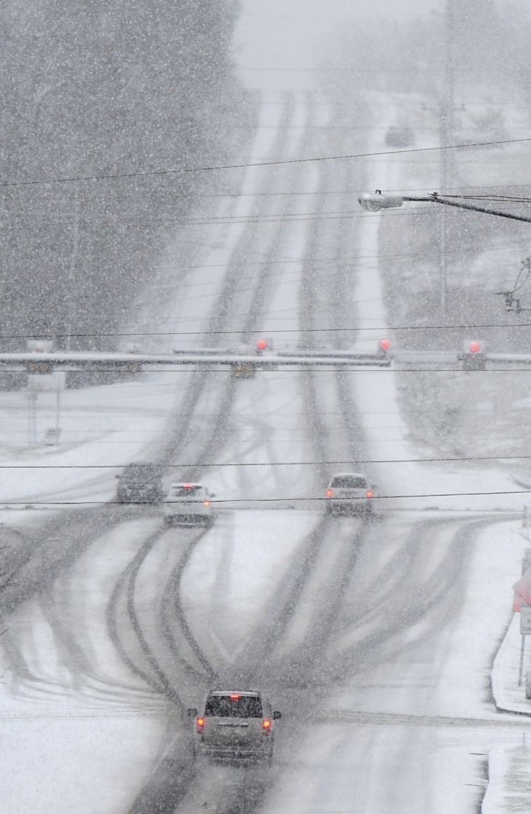 Image: Drivers make their way through falling snow in Franklin, Tenn.