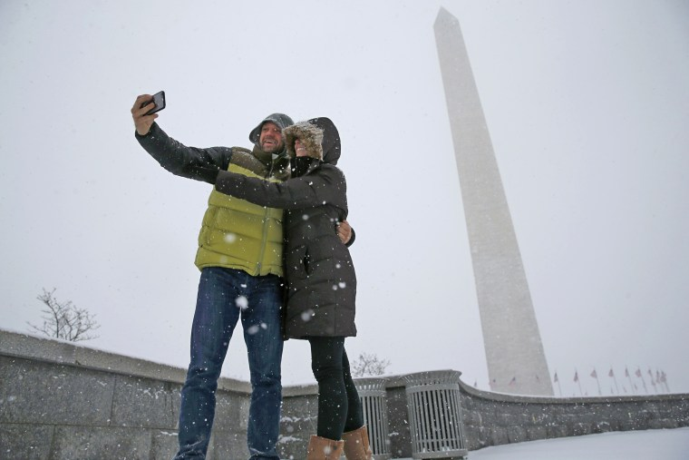 Image: A couple pauses to take a 'selfie' in the freshly fallen snow near the Washington Monument after snowstorm arrived in Washington