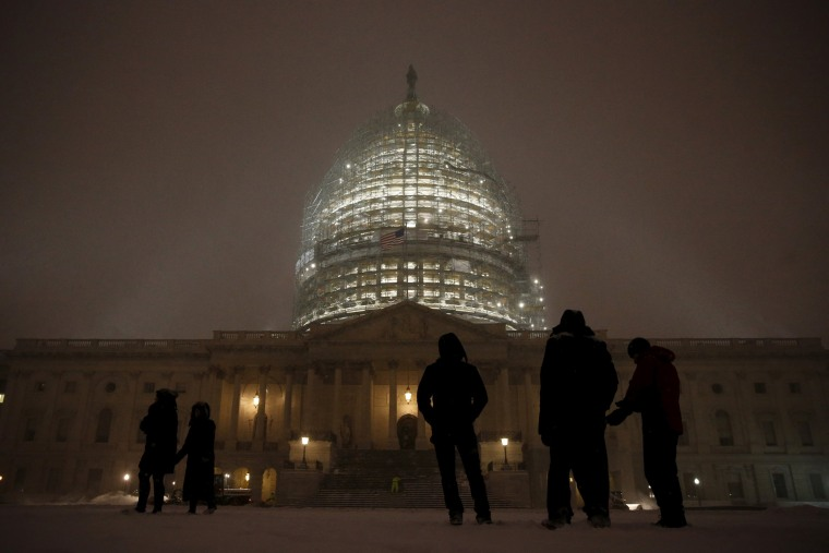 Image: People gather to watch the falling snow at the U.S. Capitol in Washington