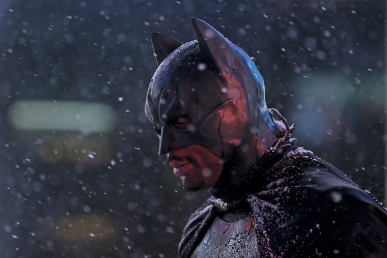 """Image: A man dressed as \""""Batman\"""" stands as it begins to snow in Times Square in the Manhattan borough of New York"""