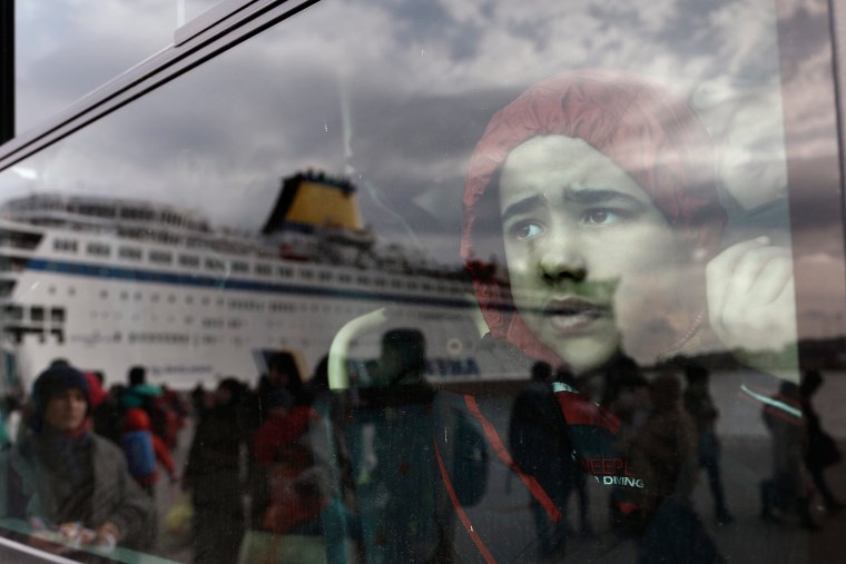 Image: Refugees and migrants arrive at the port of Piraeus, near Athens