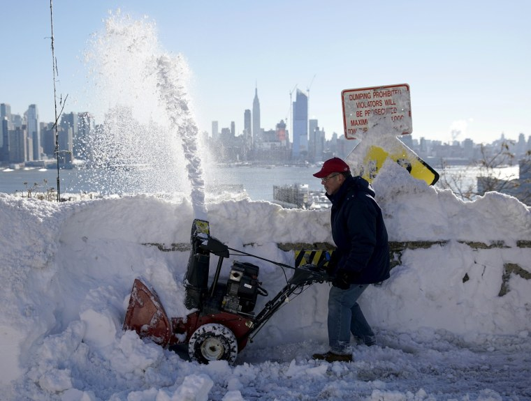 Image: A resident removes snow away from the entrance to his home in Union City