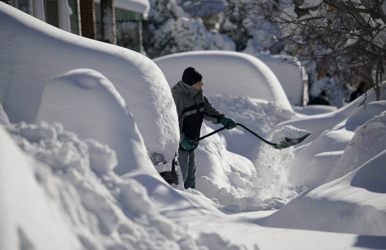 Image: A resident shovels snow away from the entrance to his home in Union City