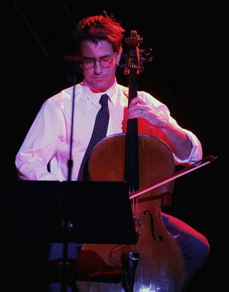 """Actor Mulroney plays the cello as he performs with singer LeAnn Rimes at The Trevor Project's """"Trevor Live"""" fundraising dinner in Hollywood"""