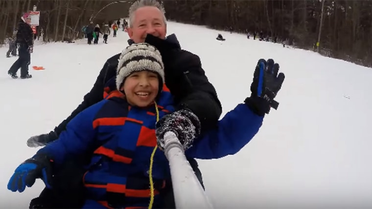 Ontario policeman David McNab has fun sliding down a hill in Peterborough, Ontario, with one of three Syrian refugee children that he and a group of local citizens are helping acclimate to life in Canada.