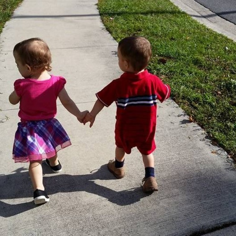 twin siblings holding hands