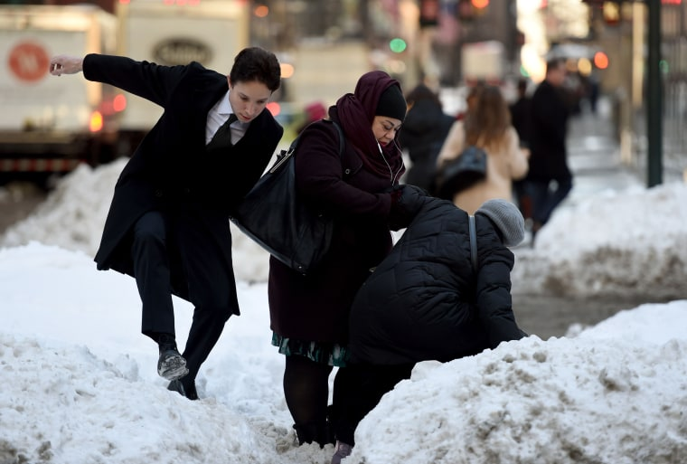 Image: People try to navigate a snowbank in the middle of Park Avenue