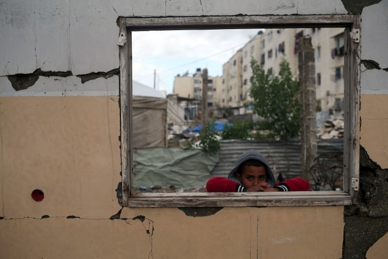 Image: A Palestinian boy looks on from the window of a building