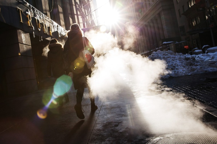Image: A woman walks through a cloud of steam two days after a massive snow storm covered the East Coast