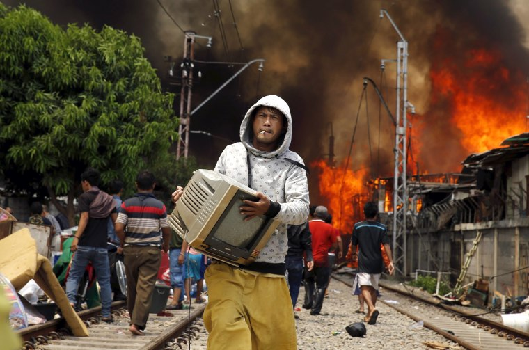 Image: A man carries a television away from a fire in a slum area next to railway tracks in Kampung Bandan, North Jakarta, Indonesia