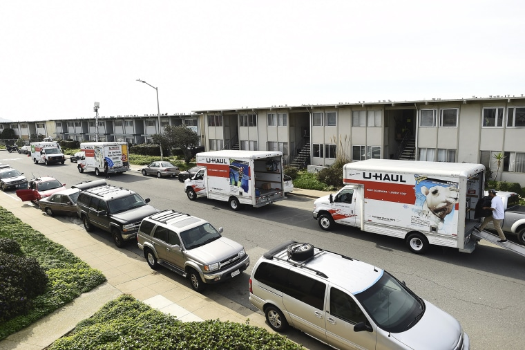 Image: Moving trucks line a street as residents evacuate from an apartment complex which in danger of collapsing due to El Nino storm erosion in Pacifica