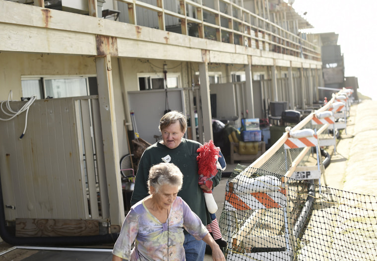 Image: Garth Yeaman and his friend Janet Breger walk along a crumbling cliff outside his apartment building, which is in danger of collapsing due to El Nino storm erosion, in Pacifica, California