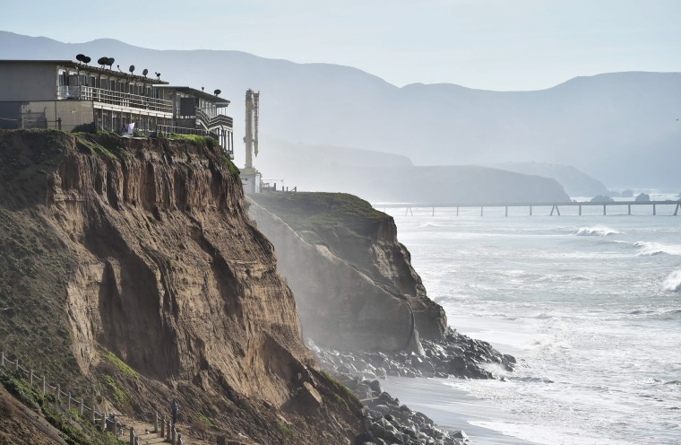 Image: Apartments are seen at the edge of an eroding cliff while residents evacuate in Pacifica