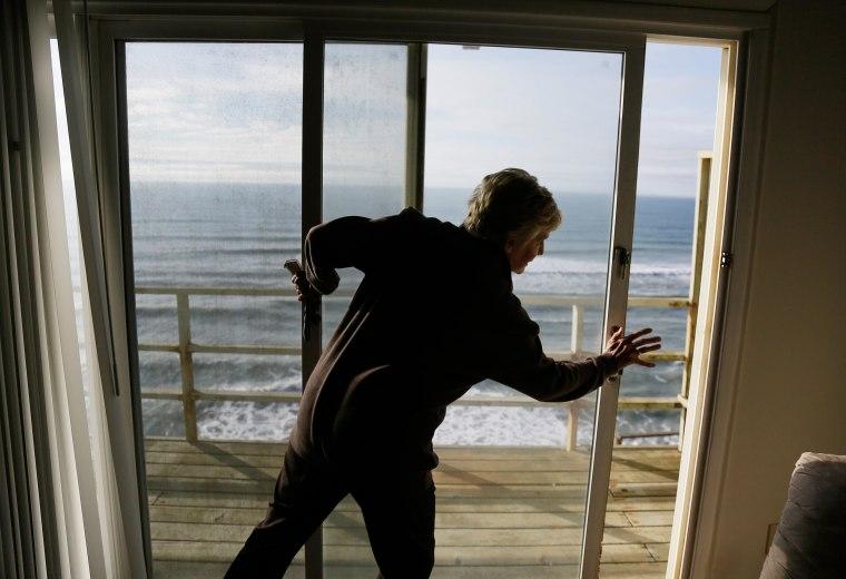 Image: Eileen Horan shuts the door to her patio overlooking the Pacific Ocean