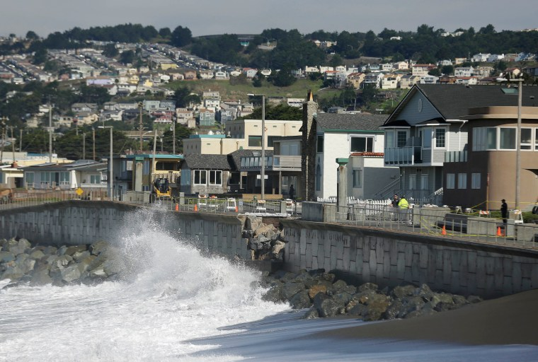 Image: Waves crash near a damaged section of the seawall