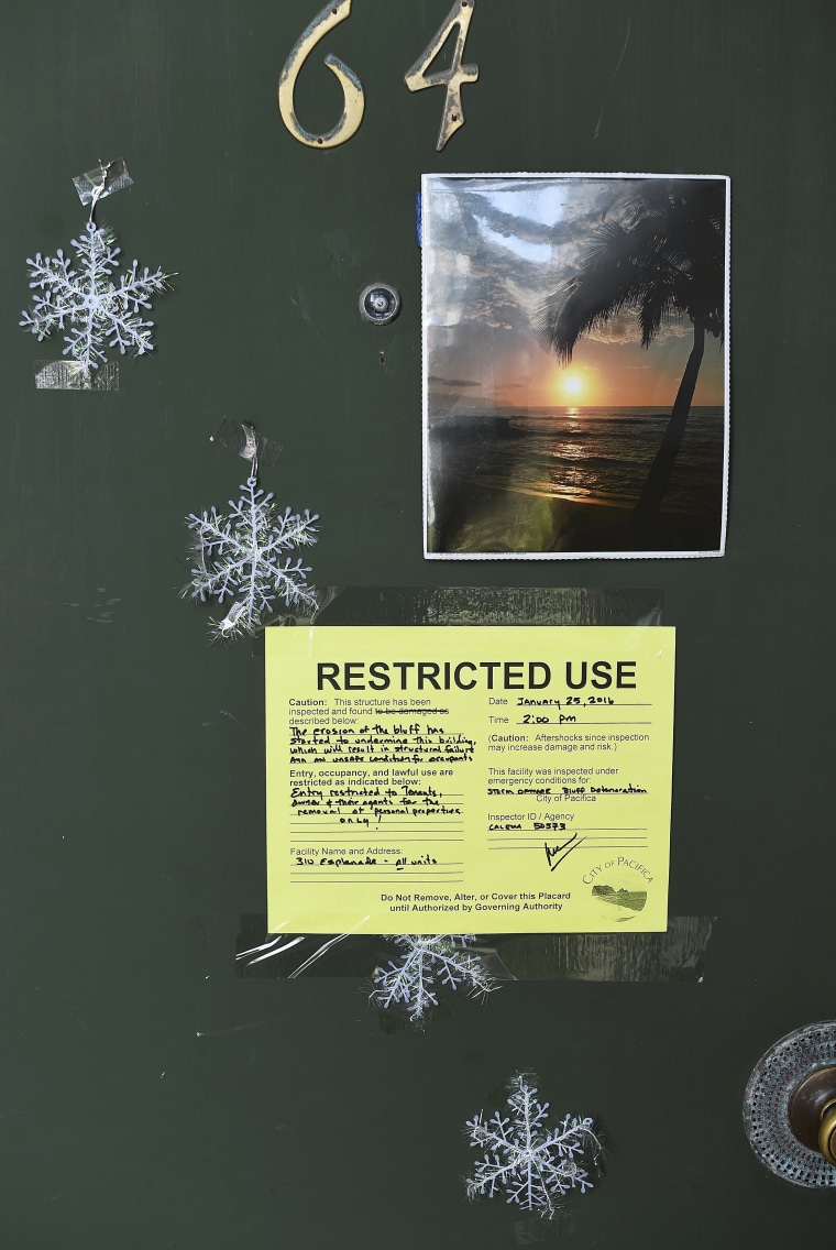 Image: A warning notice is pictured on a door at an uninhabitable apartment, in danger of collapsing due to storm erosion, in Pacifica