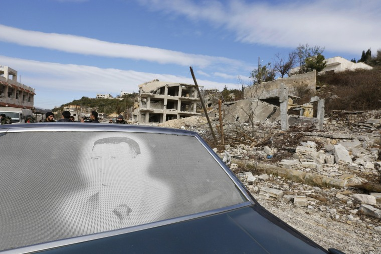 Image: An image of Assad is seen on a car parked in front of damaged buildings in the town of Rabiya