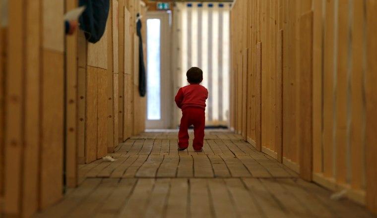Image: A migrant child walks through the first registration camp of Erding near Munich