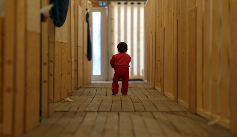 Image: A migrant child walks through the first registration camp of Erding near Munich