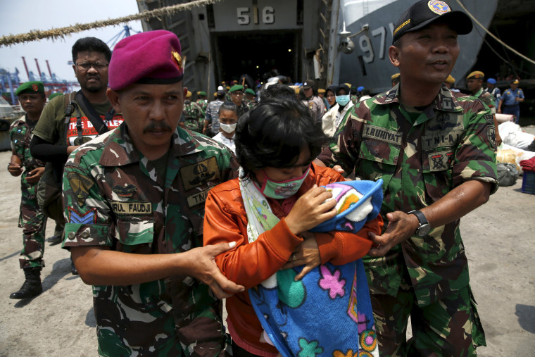 Image: Indonesian Navy personnel assist a member of Gafatar sect disembark from the KRI Teluk Banten naval ship