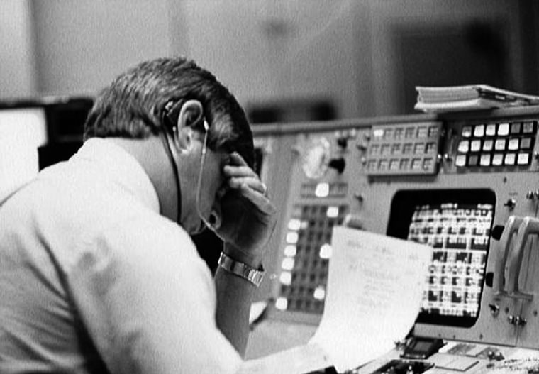 Image: Flight director Jay Greene studies data at his console inside Johnson Space Center's Mission Control Center