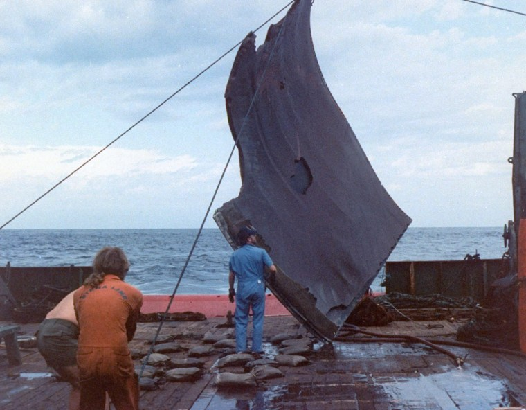 Image: A piece of debris from the space shuttle Challenger is hoisted onto the deck of the Stena Workhorse