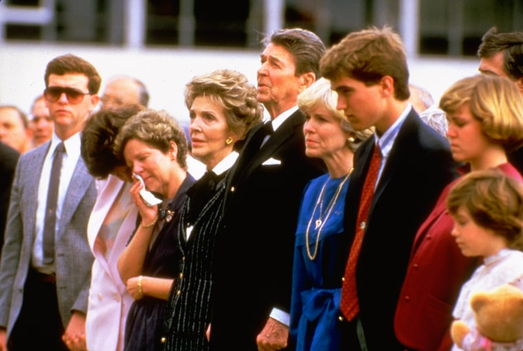 Image: President Ronald Reagan and his wife stand with the wife of astronaut Michael Smith and other family members at a memorial service