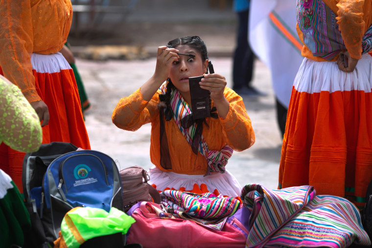 Image: Andean woman in traditional dress, applies mascara before the carnival in Ayacucho