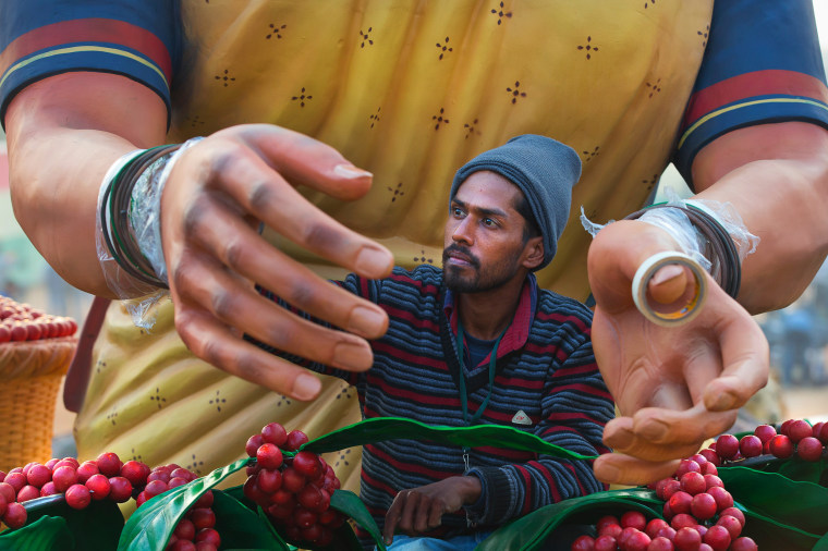 Image: An Indian worker paints the hand of a huge clay model of a tribal woman