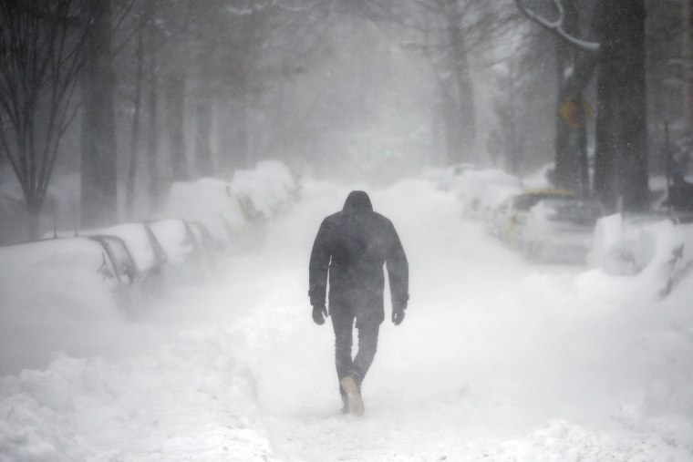 Image: A man walks along a street covered by snow during a winter storm in Washington