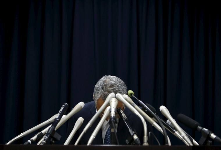 Image: Japan's Economics Minister Amari bows during a news conference in Tokyo