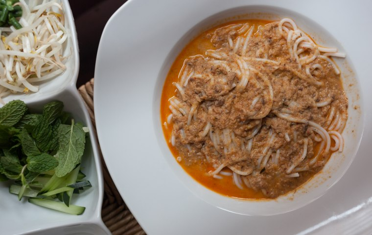 Nyoam noodles consist of a curried fish sauce atop rice noodles, eaten with mint, cucumber, and sprouts.