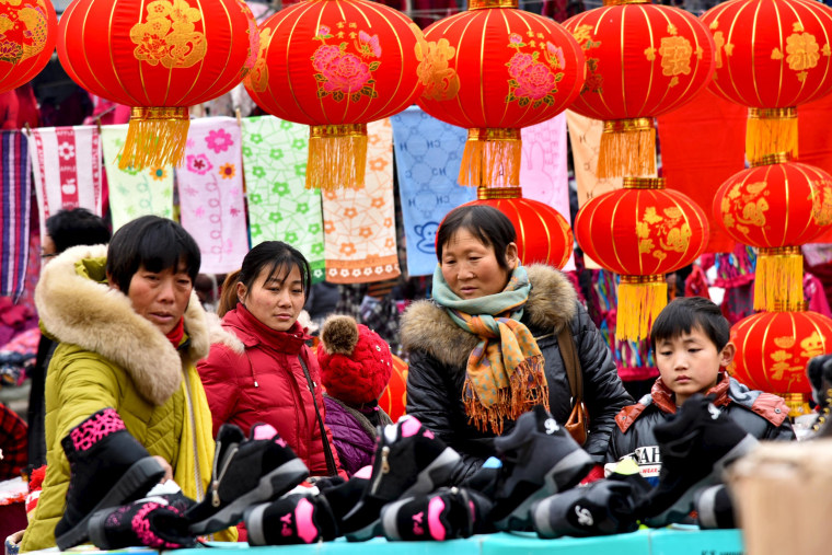Image: People shop at a new year market ahead of the upcoming Spring Festival in Zaozhuang
