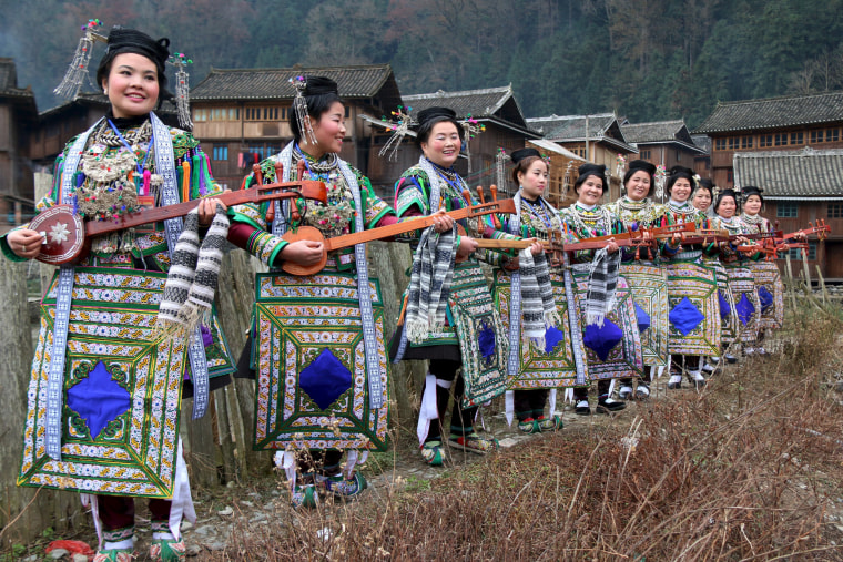 """Image: Ethnic Dong women wearing traditional costumes, hold \""""pipas\"""", a traditional instrument"""