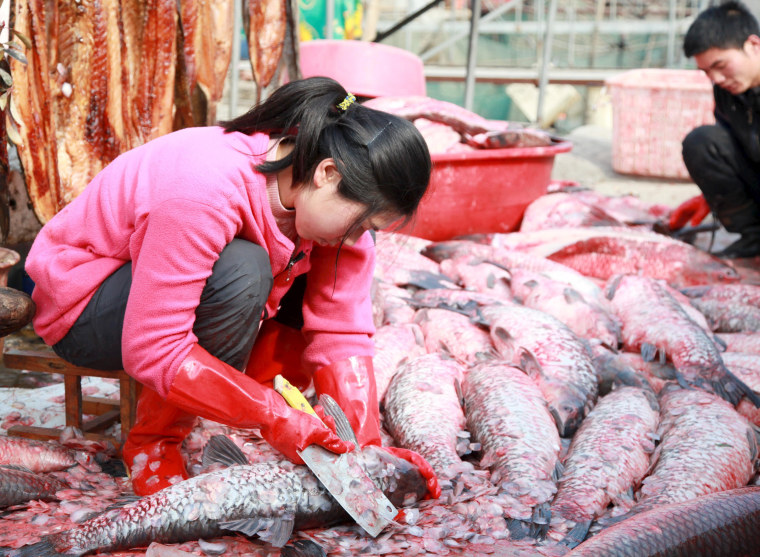 Image: A woman scales fish by the side of a lake
