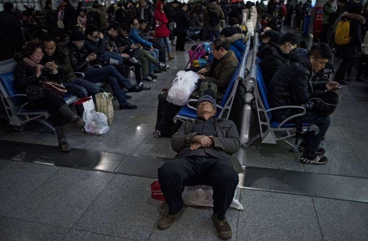 Image: Passengers wait to board their trains as they head to their hometowns