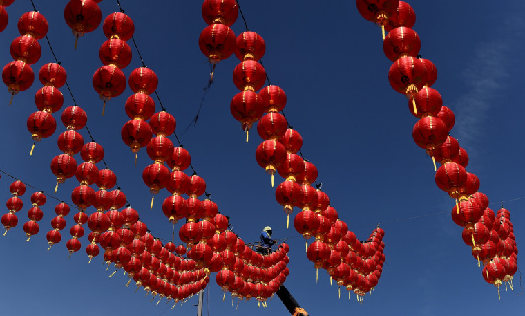 Image: A Malaysian worker puts up traditional Chinese lanterns
