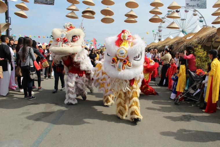 Vietnamese lion dancers make their way under the cultural village's back gate.