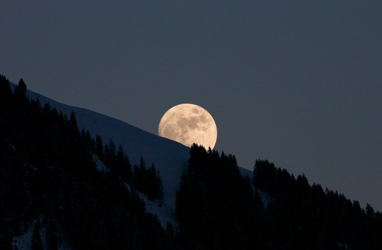 Image: Moon rises above the trees near the Streif course in Kitzbuehel