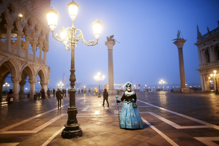 Image: A masked reveller poses during the Venice Carnival, in Piazza San Marco