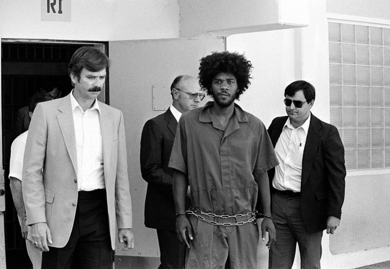 Kevin Cooper, center, a suspect in connection with the slashing death of four people in Chino, is escorted to a car for transport to San Bernadino from Santa Barbara, Calif., after he was arrested by police at Santa Cruz Island, July 31, 1983.