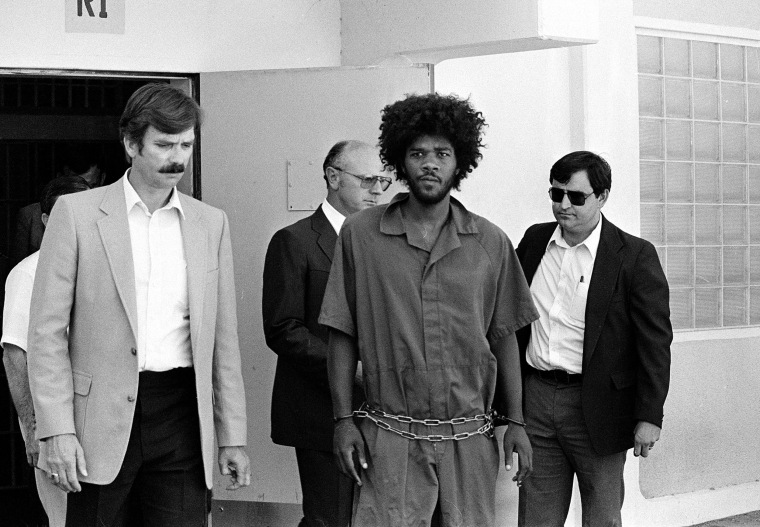 Kevin Cooper is escorted to a car for transport in 1983.