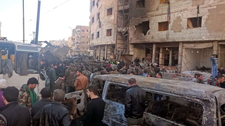 Image: Residents and soldiers loyal to Syria's President Bashar al-Assad inspect damage after a suicide attack in Sayeda Zeinab