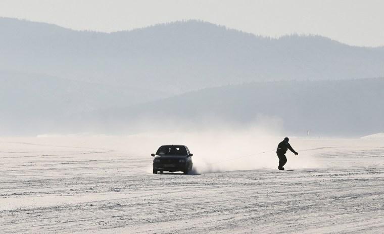 Image: Car tows snowboarder along frozen surface of Yenisei River in Taiga district outside Krasnoyarsk