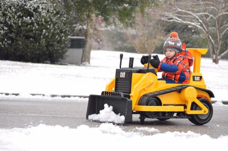 Little boy plows snow